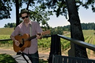 Musician Jon Ransom play guitar on the deck at the Vista Hills Vineyard, Yamhill County, Oregon